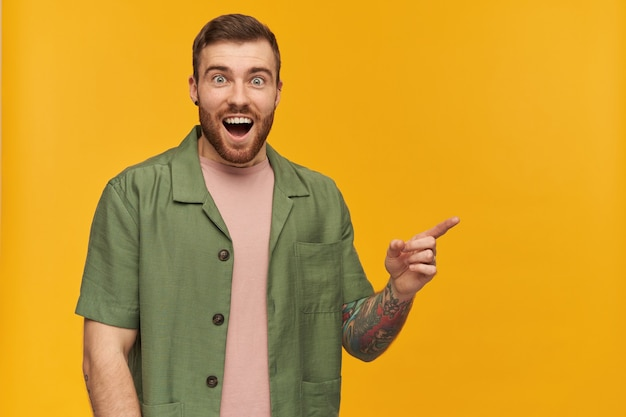 수염 난 남자, 갈색 머리를 가진 흥분된 남자. 녹색 반팔 재킷을 입고. 문신이 있습니다. 노란색 벽 위에 고립 된 복사 공간에서 오른쪽으로 손가락을 가리키는