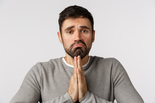 Bearded guy in grey sweater supplicating