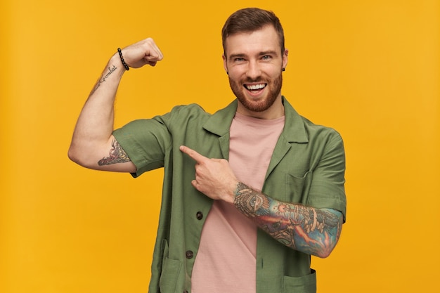 Bearded guy, happy looking man with brunette hair. wearing green short sleeves jacket. has tattoo. showing his power and pointing at biceps.  isolated over yellow wall