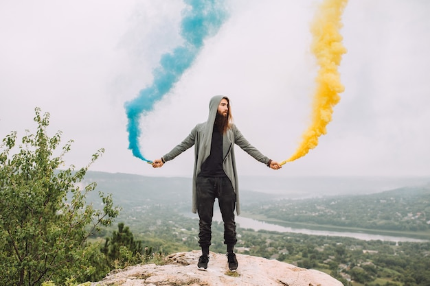 Бородатый парень держит цветной дым желтый и синий.