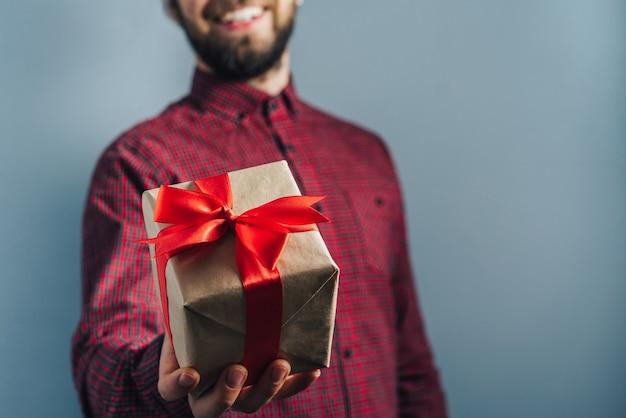 Бородатый парень держит в руках подарок, завернутый в крафт-бумагу и украшенный красной лентой.
