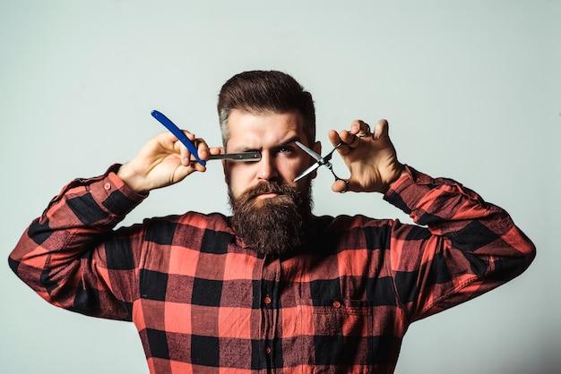 Бородатый парень держит профессиональные инструменты