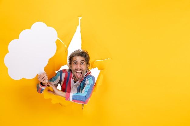 Ragazzo barbuto che tiene carta bianca a forma di nuvola e si sente felice in un buco strappato e sfondo libero in carta gialla