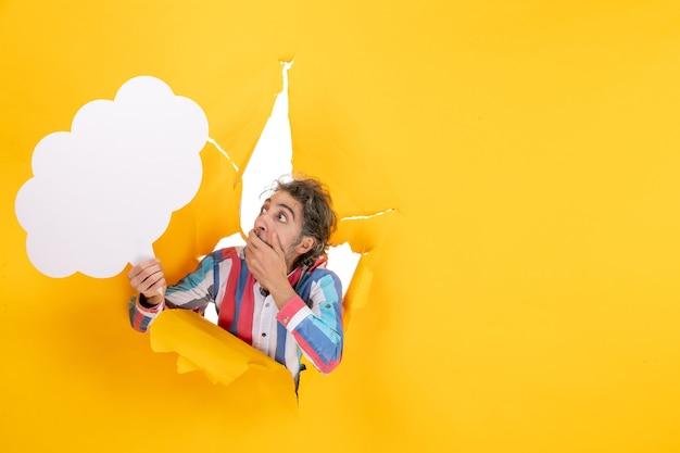 Ragazzo barbuto che tiene carta bianca a forma di nuvola e ha paura di qualcosa in un buco strappato e sfondo libero in carta gialla