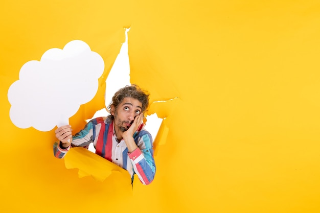 Bearded guy holding white cloud-shaped paper and thinking deeply in a torn hole and free background in yellow paper