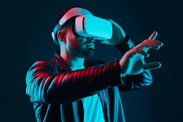 Бородатый парень в черной кожаной куртке и очках виртуальной реальности взаимодействует с невидимым экраном, испытывая виртуальную реальность в темной студии с неоновыми огнями