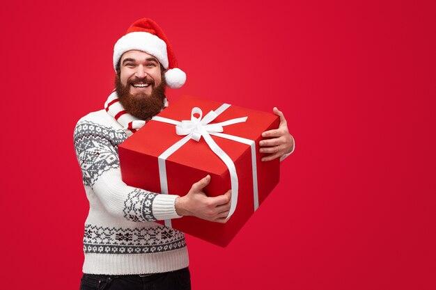 笑ってプレゼントボックスを持ってクリスマス帽子のひげを生やした男