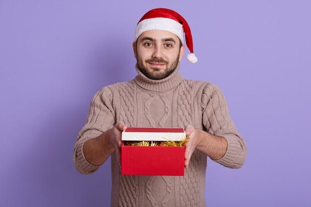Бородатый парень в новогодней шапке и бежевом свитере приносит подарки в красной коробке, позирует изолированно на фиолетовом
