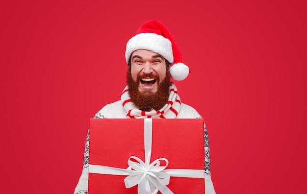 巨大なプレゼントを持っているサンタ帽子のひげを生やした男