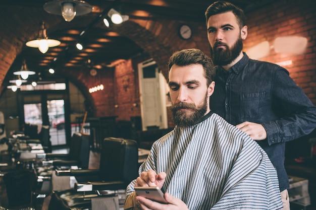 Бородатый парень сидит в кресле и готовится к процедуре. он смотрит на телефон. он очень сосредоточен. парикмахер готов начать процедуру.