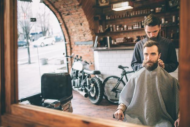 Бородатый парень сидит в кресле и смотрит в зеркало. его парикмахер готовит его подстричься.