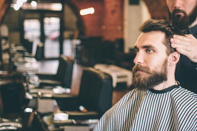 Бородатый парень сидит в салоне. его парикмахер моделирует его волосы. парень смотрит прямо вперед.