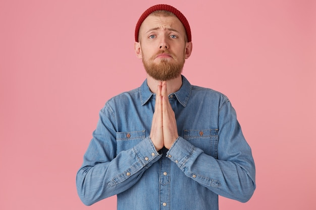 Bearded guy looks with hope, palms folded in a prayer gesture, beggs for giving good advice, asking for help from higher powers, protection, blessing, wearing a denim shirt, isolated on a pink wall