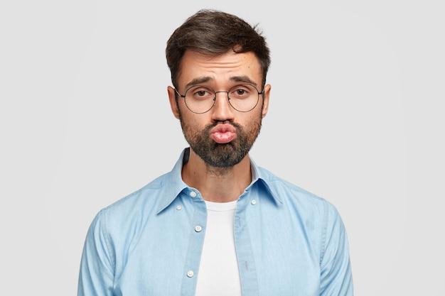 Il ragazzo barbuto fa una smorfia, tiene la bocca rotonda, ha una folta barba incolta, vestito con una camicia alla moda