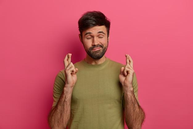 ひげを生やした男は運のジェスチャーをし、希望を持って指を交差させ、重要なニュースを予期し、目を閉じて、カジュアルなtシャツを着て、願い事をし、忠実な表現をし、バラ色の壁の上に屋内に立っています