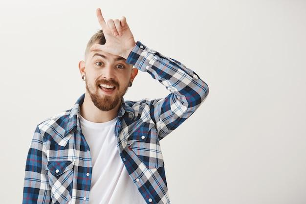 Бородатый парень издевается над кем-то жестом неудачника