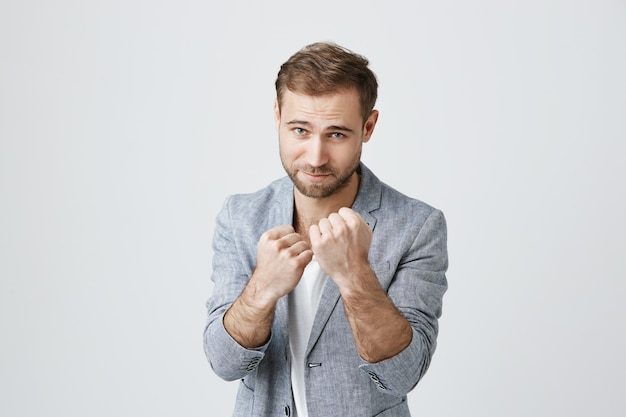 Bearded guy ready to fight, clench fists, stand boxer pose Free Photo