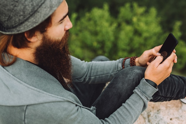 Bearded guy sits on top of a mountain amid a green landscape and holds a smart phone