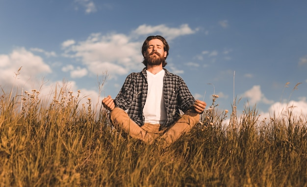 Bearded guy sitting crossed legged in meadow and meditating