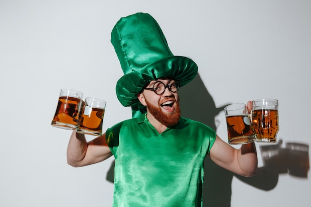 Bearded guy in st.patriks costume holding many cups