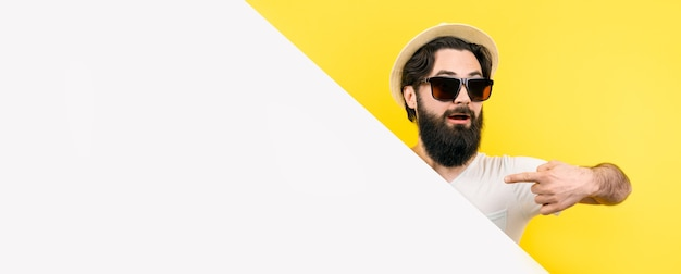 Bearded guy in sunglasses and hat, looking out from behind the empty banner