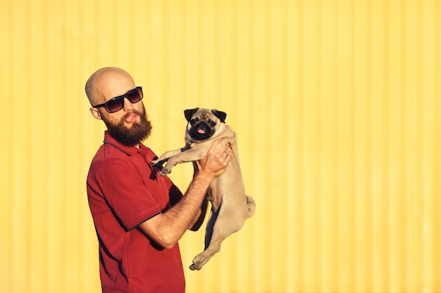 Bearded guy in sunglasses is holding pug puppy in his arms against a yellow wall