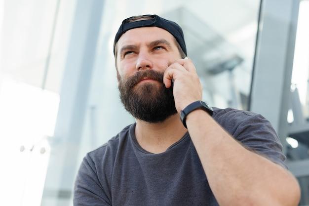 전화 통화 하는 수염 난된 남자입니다. 도시 배경에서 전화 통화를 하는 힙스터 청년