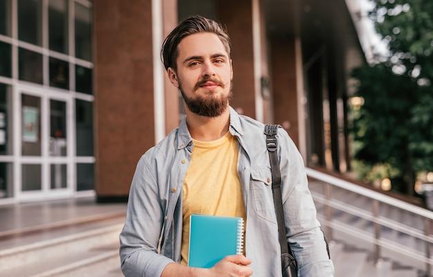 Бородатый парень с блокнотом стоит на университетской лестнице