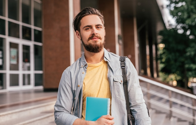 Bearded guy with notepad standing on university staircase