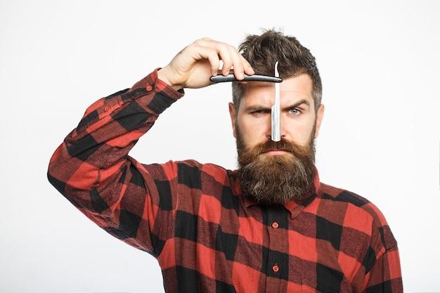 スタイリッシュな服を着たひげを生やした美容師は、理髪店に立っている間、ストレートかみそりを持っています。