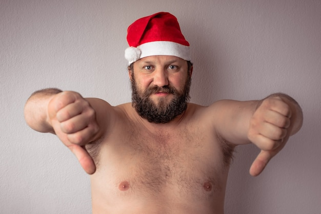 Bearded half-naked man with santa claus hat showing thumbs down against a gray wall