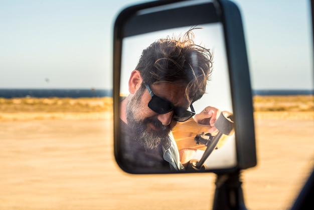 Bearded handsome adult man viewed in car mirror - summer travel adventure and active lifestyle male people with yellow desert and ocean in background - concept of journey