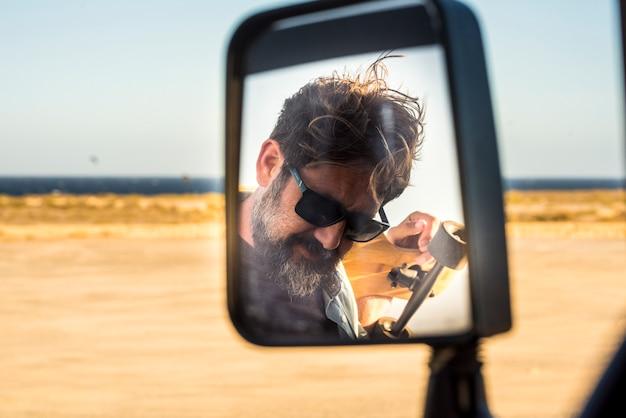車の鏡で見たひげを生やしたハンサムな大人の男-夏の旅行の冒険と背景に黄色の砂漠と海を持つアクティブなライフスタイルの男性-旅の概念