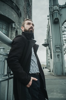 Bearded handsome guy in a brown coat and light shirt waiting for someone on the old bridge on a cloudy autumn day.