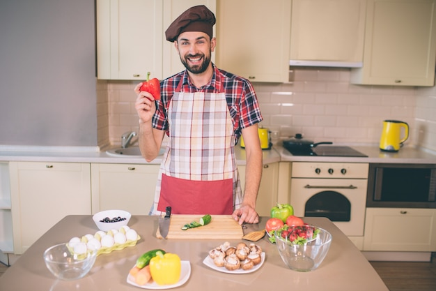 Bearded and handsome guy stands and looks. he smiles. young man holds pepper in hand. he prepares to cook. he is satisfied.