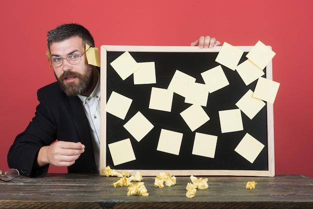 테이블에 앉아 수염을 기른 잘생긴 남성 사업가는 스티커 비즈니스에 보드를 보유