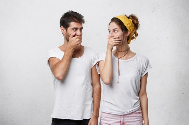 Bearded handsome male and young beautiful woman giggling together covering their mouths with hands trying to be calm looking at each other with funny look