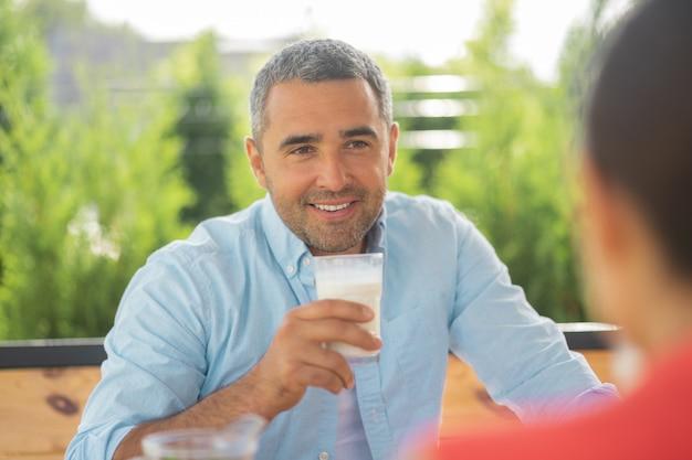あごひげを生やしたハンサムな男。朝食を食べながら彼の素敵な妻を見ているひげを生やしたハンサムな男