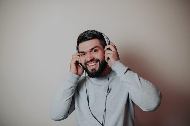 Bearded handsome man in headphones, man listening music,