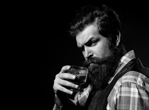 Bearded handsome man holding glass of whiskey