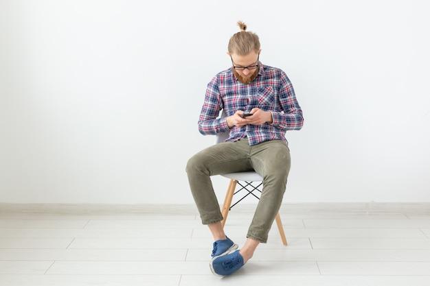 白い壁に携帯電話を見ている格子縞のシャツのひげを生やしたハンサムな男。