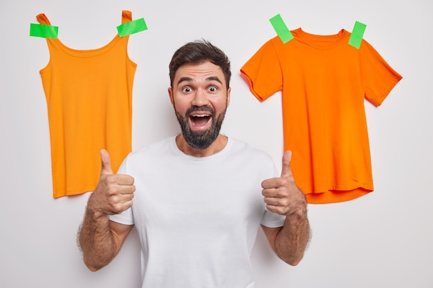Bearded handsome man keeps thumb up recommends something has positive expression dressed in casual clothes poses against white wall with t shirt and shirt plastered