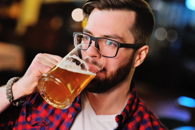 Bearded handsome man in a plaid shirt with a glass of beer