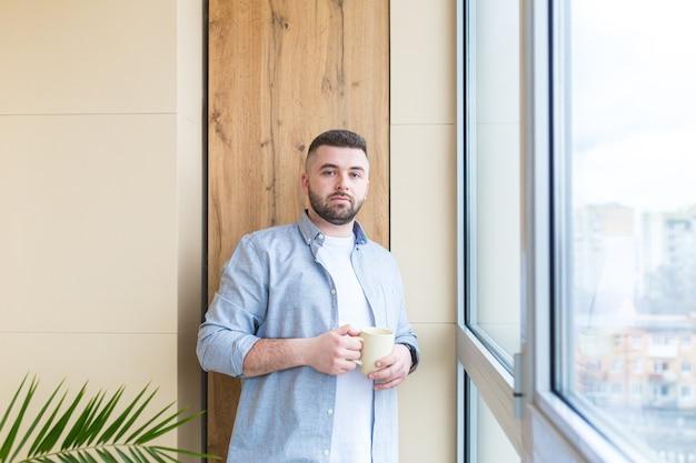 수염 난 잘 생긴 남자가 발코니에 손에 컵을 들고 창가에 서서 캐주얼 한 옷을 입은 남성이 사무실이나 집에서 휴식을 취하거나 직장에서 타임 아웃을 통해보기를 즐깁니다.