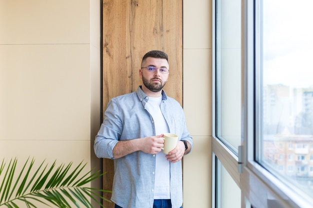 Bearded handsome man stands by window with a cup in his hand on the balcony and drinks a hot coffee or tea male in casual clothes enjoys view through in office or home relaxing or timeout at work