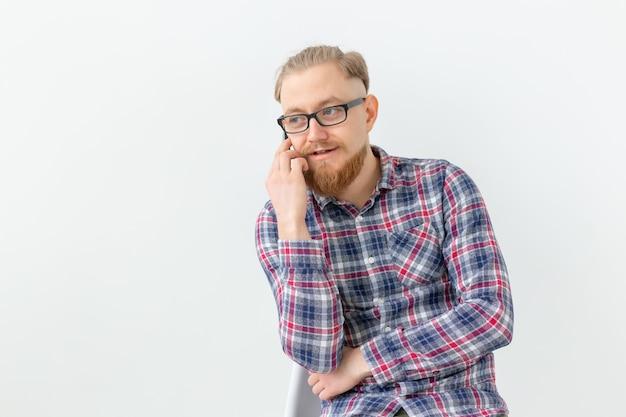 白い壁を越えて電話で話しているひげを生やしたハンサムな男。
