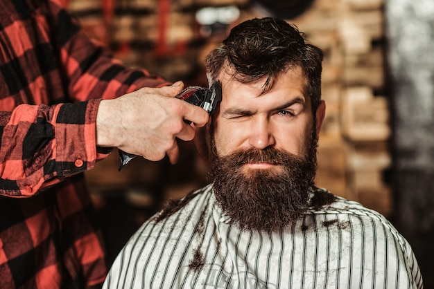 Bearded handsome man visiting hairstylist. barber shop. barber shearing beard to man. male hairstylist serving client.