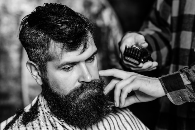 Bearded handsome man visiting hairstylist.