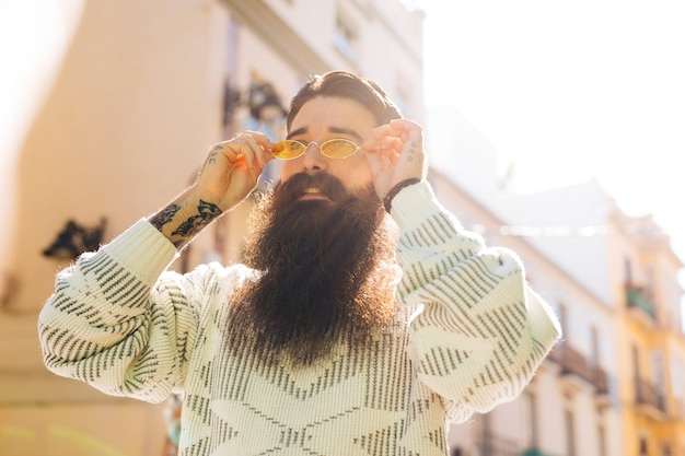 Bearded handsome young man putting on the yellow sunglasses during summer