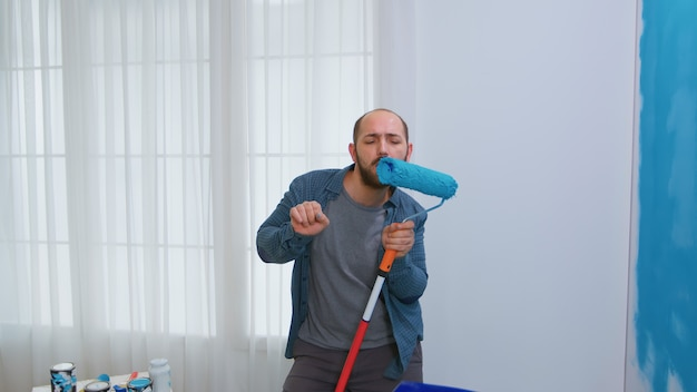 Bearded handyman singing using roller brush during home repair. apartment redecoration and home construction while renovating and improving. repair and decorating.